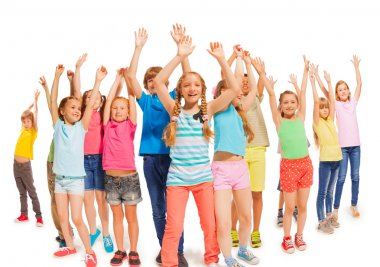 Many happy kids together raise hands up in the air