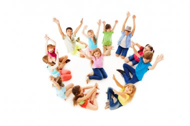 Many children in circle with boy center lift hands