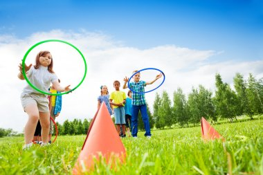Two group of kids playing with hula hoops