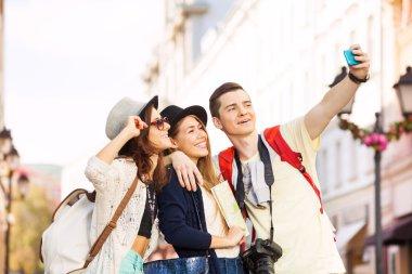 Three happy friends take selfies