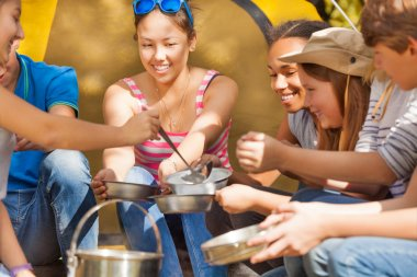 Teens pours soup in metallic plates