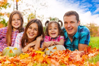 Family in autumn leaves with Halloween pumkins