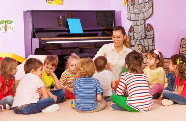 kids sit and listen to teacher tell story
