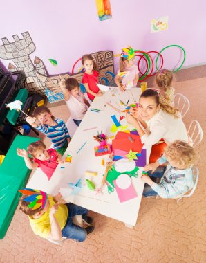 Kids around table in kindergarten