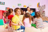Fotografie Kids listen to teacher storytelling reading book