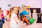 Fotografie Group of kids listen to teacher reading book