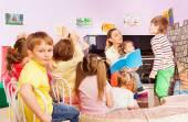 Gyerekek hallgatni az osztályban tanító olvasókönyv