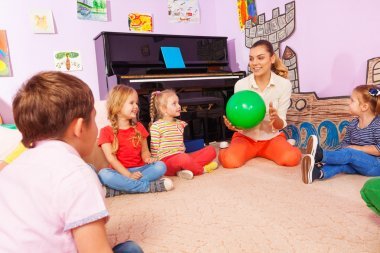 Teacher and kids sit in circle play with ball