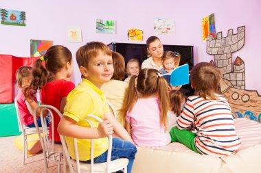 Kids listen to teacher storytelling reading book