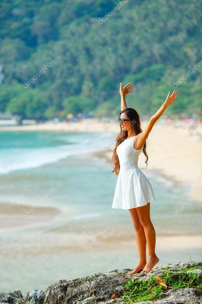 Beautiful woman in white dress at the rocks