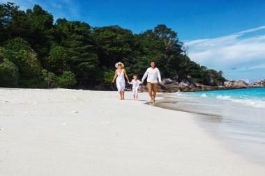 Family of three running along beach