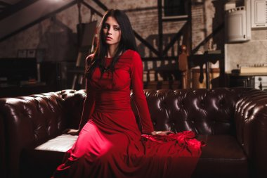 young woman in red dress sitting on leather sofa