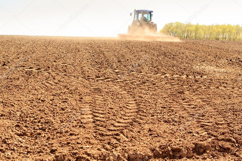 distant tractor leaves fresh track on wet ploughed field