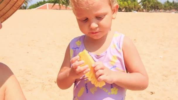 little girl eats pineapple fruit