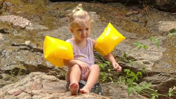 Blonďatá holčička v žluté rameno rukou