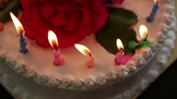 Candles burning on white creamy cake