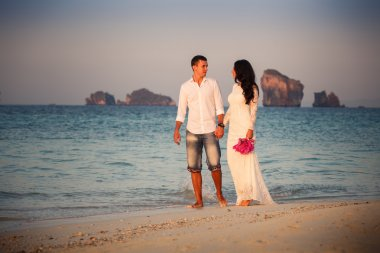 bride and groom walk  at  beach at dawn