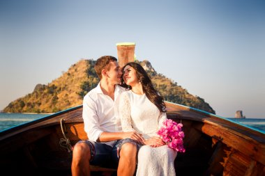bride and groom float in longtail boat