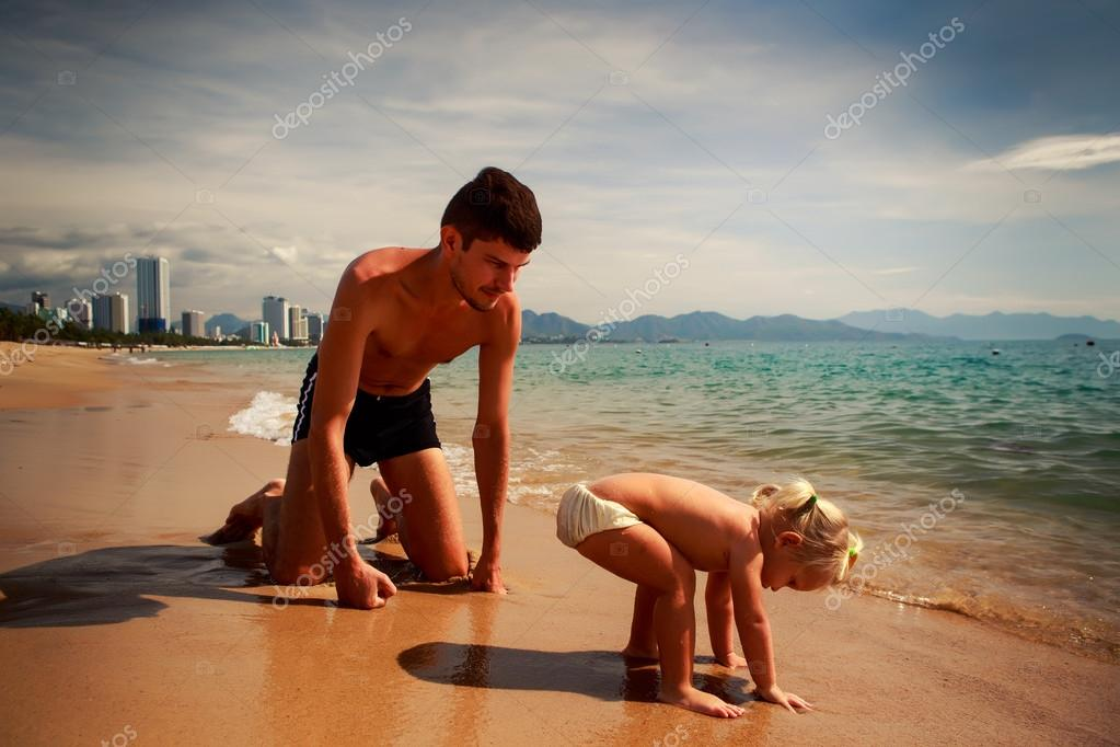father squats at little daughter near water on sand beach
