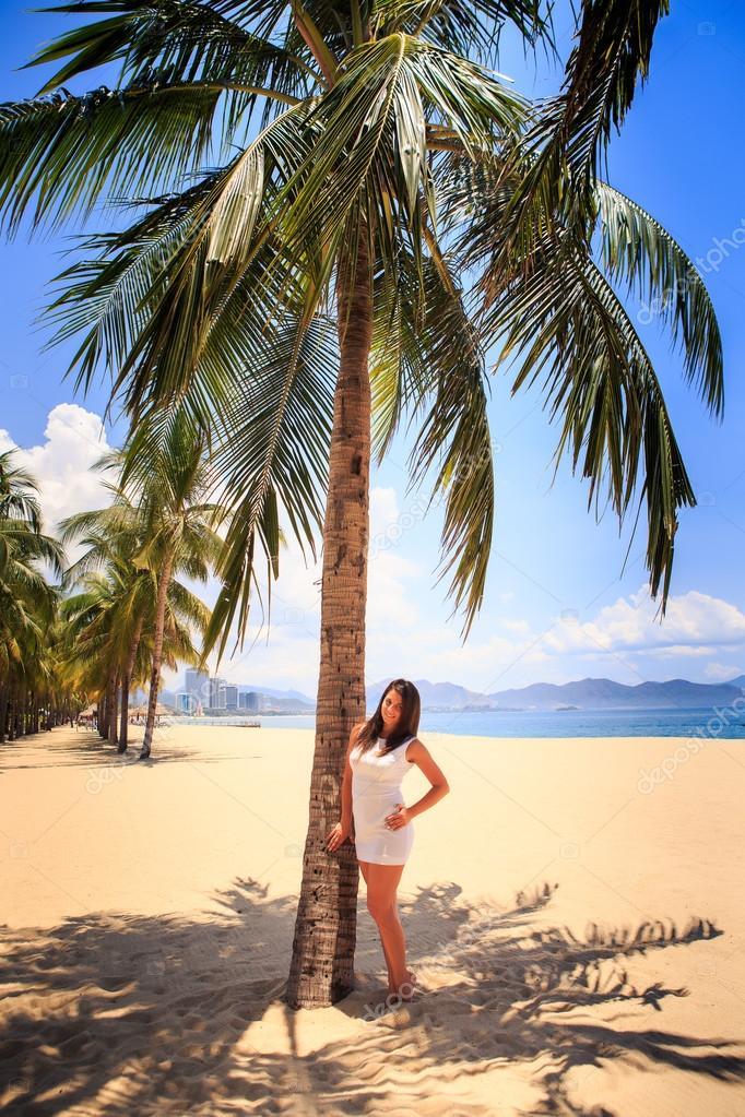 fille avec grosse poitrine dans une robe blanche se penche sur les grands palmiers sur la plage. Black Bedroom Furniture Sets. Home Design Ideas