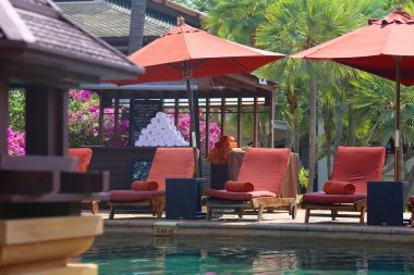 The invited shade of the beach pool umbrella pool beds with spa towels in the pool area on the territory of the tropic hotel in Thailand, Phuket island
