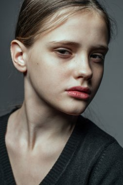 Close-up face portrait of young woman without make-up.
