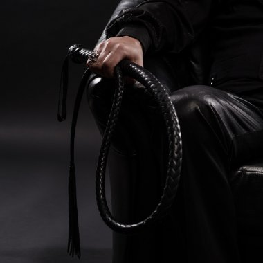 male hand holding black leather whip