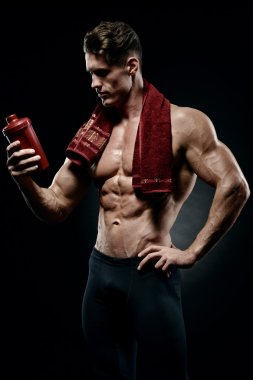Muscular fitness male bodybuilder holding protein shake bottle