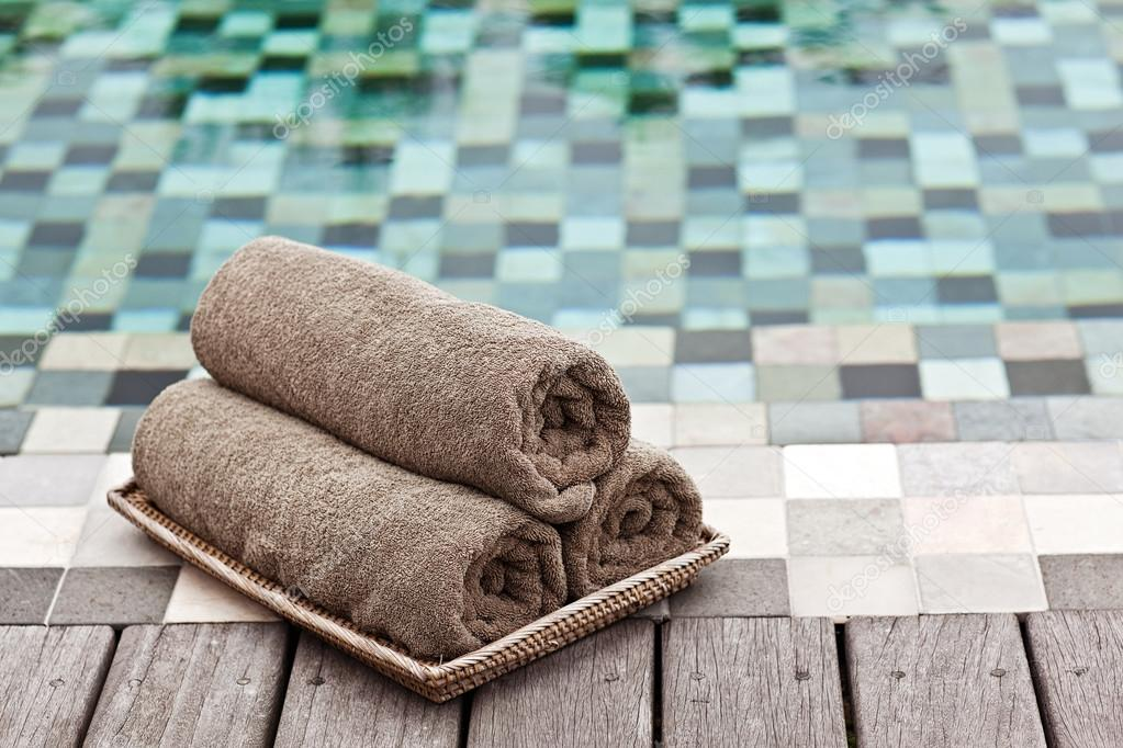 Brown towels in wicker basket at a luxury swimming pool — Stock ...
