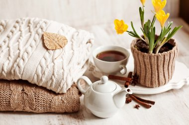 Cup of hot drink, knitting clothes, cinnamon and flowers. winter mood