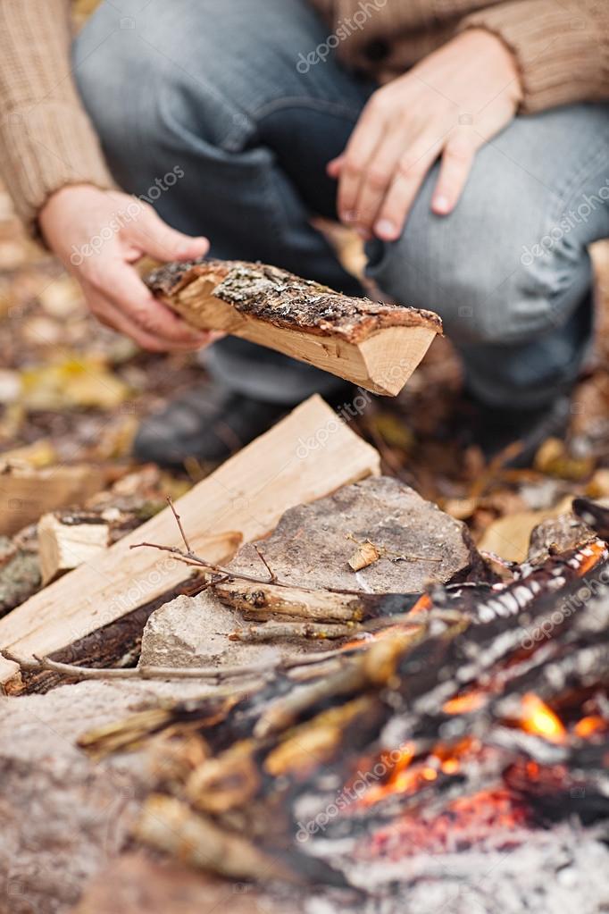 Hand putting fir wood to fire
