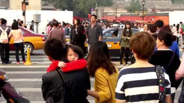 People cross the street in spite of the traffic light in Beijing, China