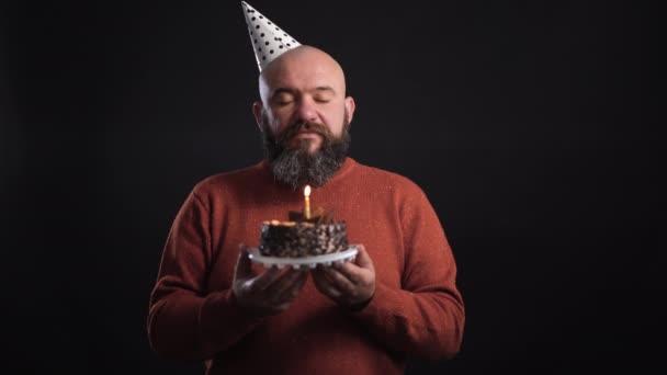 vousatý muž na černém pozadí v slavnostní čepici a drží dort otevře oči a sfoukne svíčku