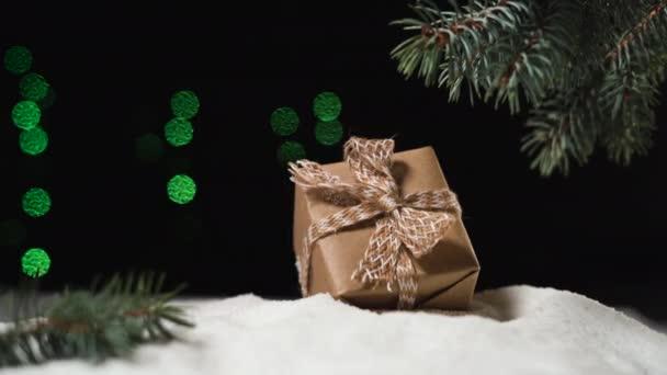 ve sněhu pod stromem leží krabice zabalená v červím papíru. Ženská ruka ji vezme