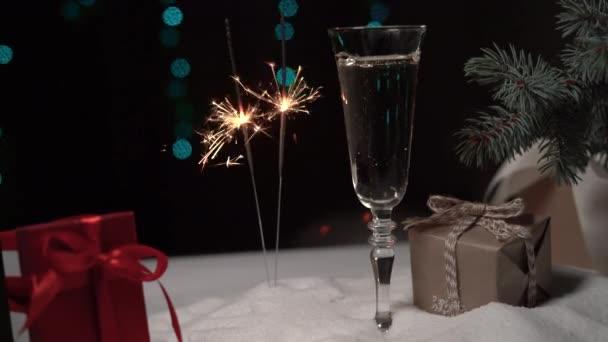 ve sněhu stojí sklenice šampaňského, vedle sebe hoří dva jiskry