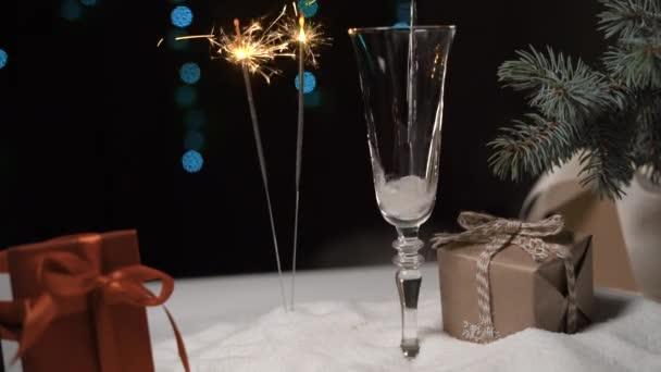 a ragyogó égő csillagszórók hátterében pezsgőt öntenek egy pohárba