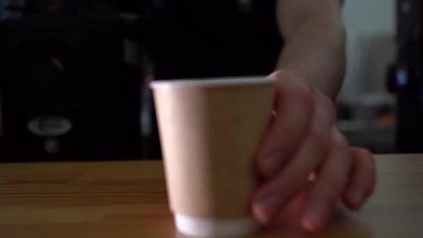 barista mozog egy fa asztal Tea vagy kávé, eszpresszó, latte, elvitelre cappuccino. közelkép A csészére fókuszálva