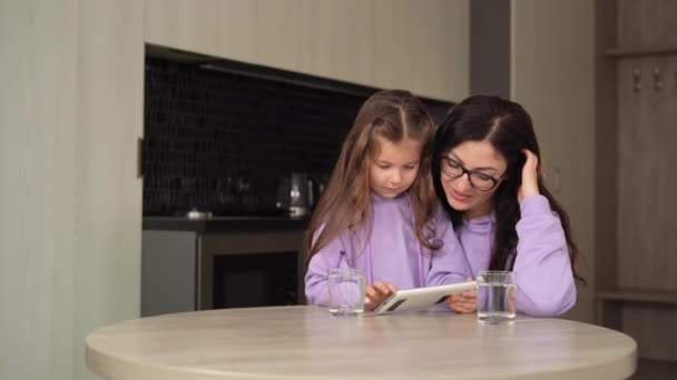 A brunette with black-rimmed glasses sits at the kitchen table with a tablet in her hands, next to her is a little daughter, 6 years old, with long hair.