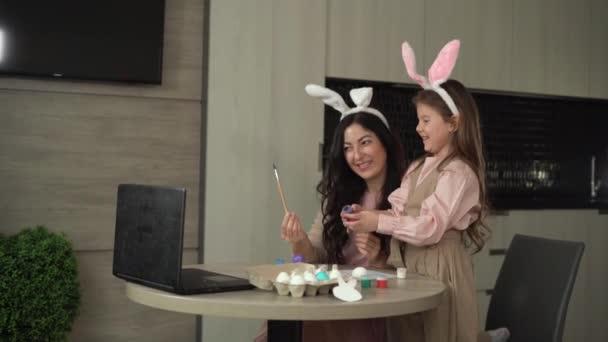 Frohe Ostern. Eine fröhliche Familie bereitet sich auf die Osterfeiertage vor, Mutter und Tochter bemalen Eier, kommunizieren per Video mit Freunden.