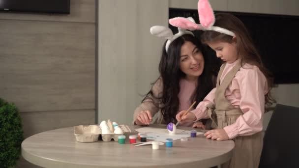 Frohe Ostern. Eine fröhliche Familie bereitet sich auf die Osterfeiertage vor. Mutter und Tochter bemalen Eier, spielen mit Farben. Sie sitzen zu Hause