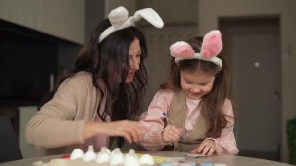 Boldog húsvétot! Vidám család készül húsvéti nyaralás anya és lánya öltözött nyúl füle készülj tojást festeni.