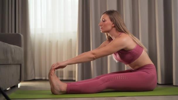 Sportovní mladá žena ve sportovním oblečení dělá fitness strečink doma v obývacím pokoji. Sportovní a rekreační koncept
