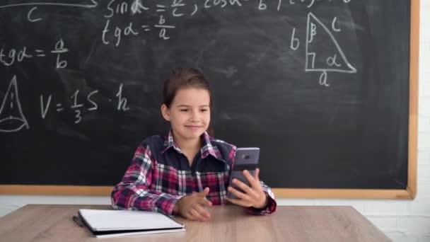 Kavkazská školačka sedí u stolu na pozadí křídového prkna. Vytáhne telefon a udělá videohovor. zpátky do školy. Pohyb fotoaparátu.