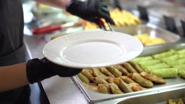 Ruce číšníka v černých rukavicích se a dát jídlo na talíř v jídelně nebo bufetu. Pelety plněné masem.