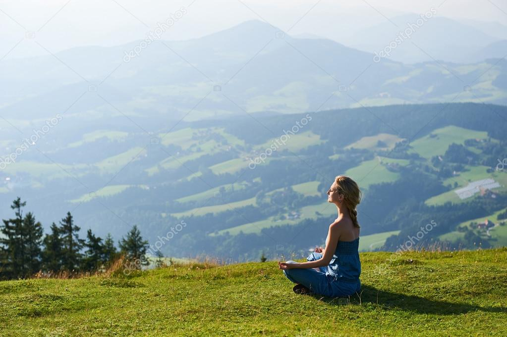 Young woman practice yoga on mountain peak