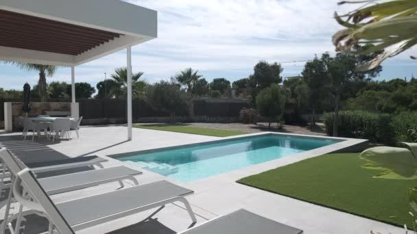 Luxus-Sommervilla mit Pool und leeren Liegestühlen in Reihe an warmen Sommertagen. Urlaub und neue Immobilien, Bankkredite, Bausparkonzept. Spanien