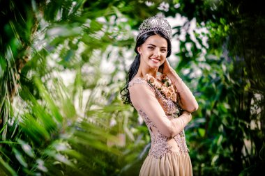 Elegant smiling lady with tiara on a head posing in a forest