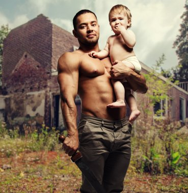 Father hugging a baby and holding a sword