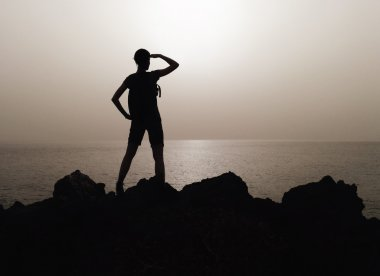 Silhouette of woman on a top of mountain