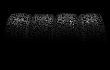 Car tires over black background